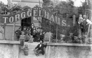 Eine Weingesellschaft mit Kind und Kegel posiert dem Fotogragen vor dem neuerbauten Torggelhaus, dem heuteigen Gasthaus Zeigerle.