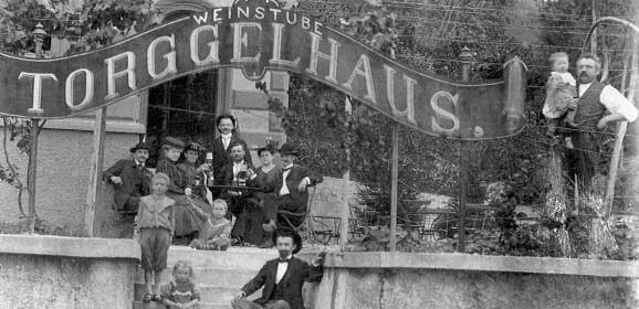 Eine Weingesellschaft mit Kind und Kegel posiert dem Fotographen vor dem neuerbauten Torggelhaus, dem heutigen Gasthaus Zeigerle.